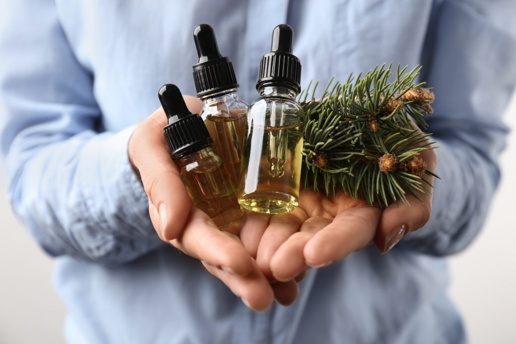 woman holding essential oils bottles and branches from Christmas tree